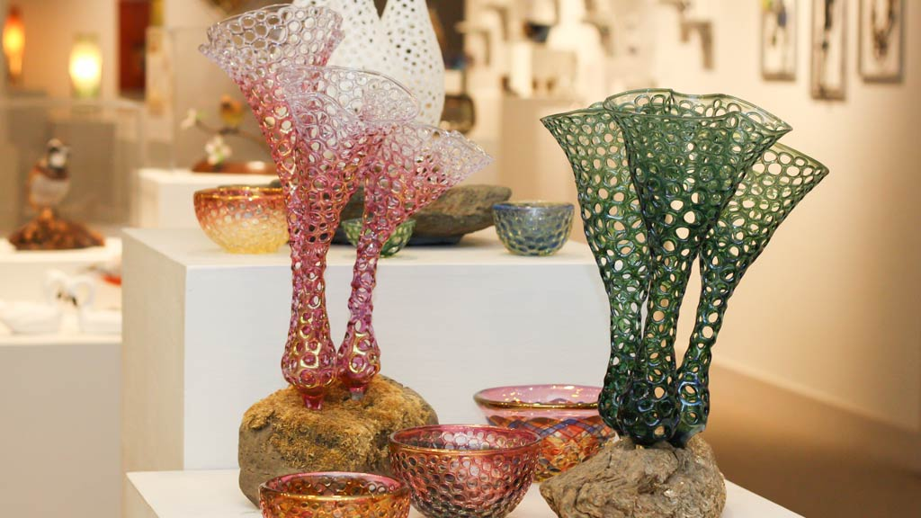 Glass works by Jason Howard in The Gallery of Fine Craft with a back drop of a variety of works the background.