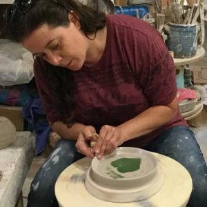 Potter, Amy Peseller shapes the edge of her pottery on a wheel.